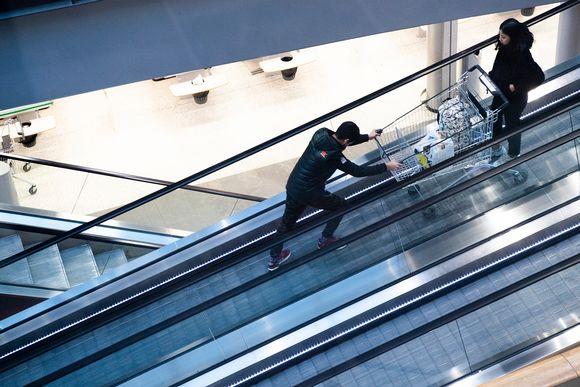 Pariskunta liukuportaissa ostoskeskuksessa.