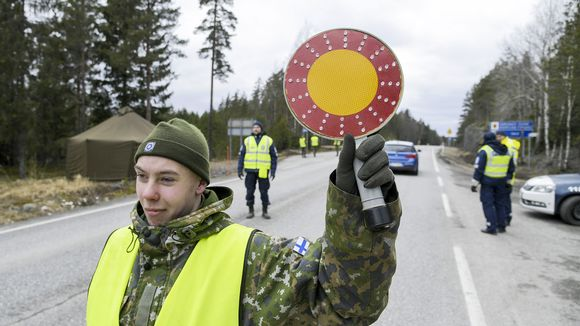 Varusmies ja poliiseja tarkastuspisteellä Uudenmaan ja Varsinais-Suomen rajalla kantatiellä 52 Raaseporissa.