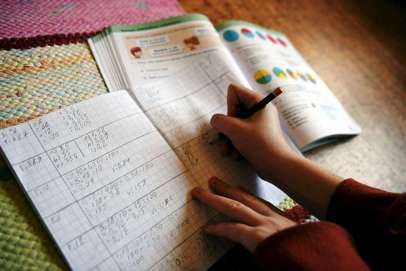 Kuvassa koululainen tekee matematiikan tehtäviä kotonaan.
