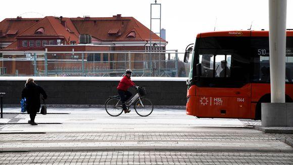 Jalankulkija, pyöräilijä ja linja-auto Pasilassa.