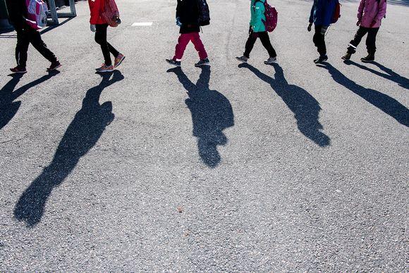 Oppilaat jonottavat Pasilan peruskoulun pihalla.