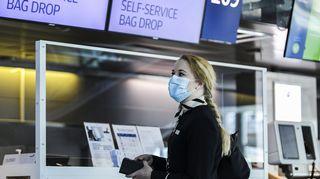 Kuvassa on suu- ja nenäsuojainta käyttävä Finnairin työntekijä.