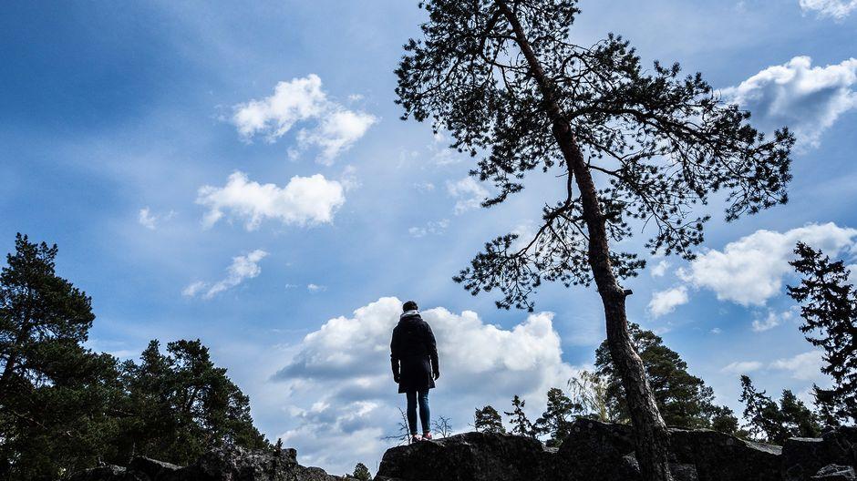 Nainen seisoo yksin kalliolla.