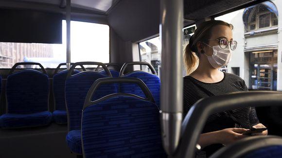Hengityssuojainta käyttävä nainen matkustaa bussilla Helsingissä.