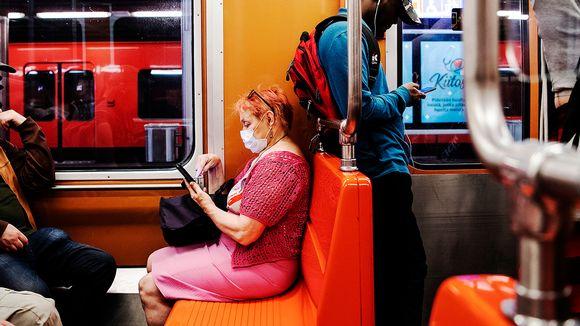 metromatkustajia, naisella maski