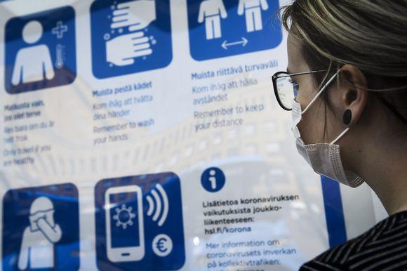 Hengityssuojainta käyttävä nainen katsoo turvallisuusohjeita bussipysäkillä Helsingissä.
