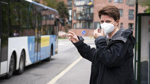Nainen viittoo bussia pysähtymään Helsingissä.