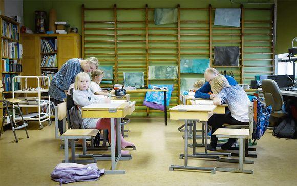 Utön alakoulussa on meneillään oppitunti. Lapset istuvat pulpeteissaan ja opettajat neuvovat tehtävissä,