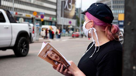 Nuori nainen maski kasvoillaan ja opinto-opas kädessään.