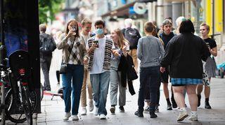 Joukko nuoria kadulla, yhdellä maski kasvoillaan.