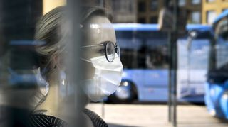 Hengityssuojainta käyttävä nainen odottaa bussia Helsingissä.