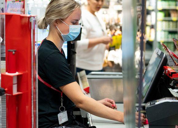 myyjä palvelee asiakasta maski päässään.