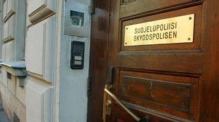 Kuvassa on Suojelupoliisin kyltti ovessa.