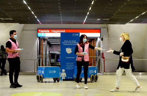 Helsingin seudun liikenteen (HSL) työntekijät jakavat ilmaisia kasvomaskeja ihmisille Tapiolan metroasemalla Espoossa 28. elokuuta 2020.