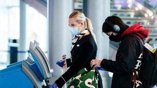 KAsvomaskiin pukeutuneita matkustajia Helsinki-Vantaan lentoasemalla.