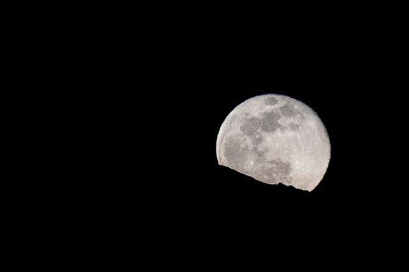 Kuu nousee vuoren rinteen takaa.