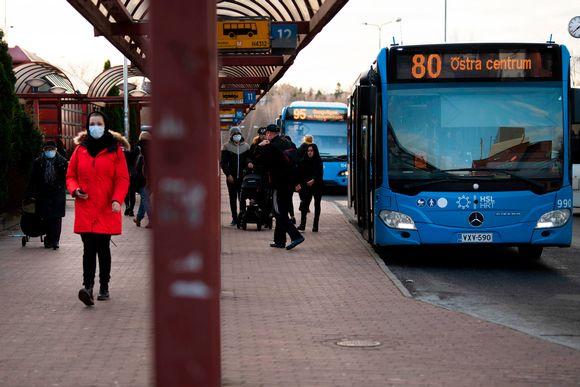 Kasvomaskeihin pukeutuneita matkustajia Itäkeskuksen bussiterminaalin edustalla.