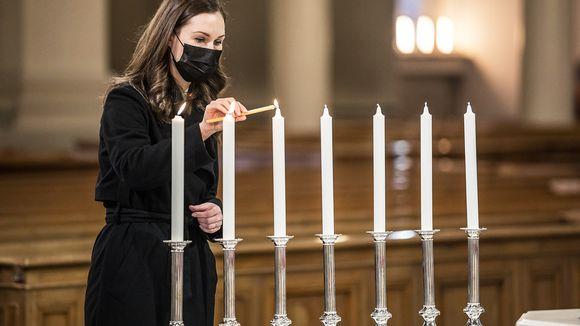Pääministeri Sanna Marin sytyttää kynttilän ennen itsenäisyyspäivän ekumeenista jumalanpalvelusta Tuomiokirkossa