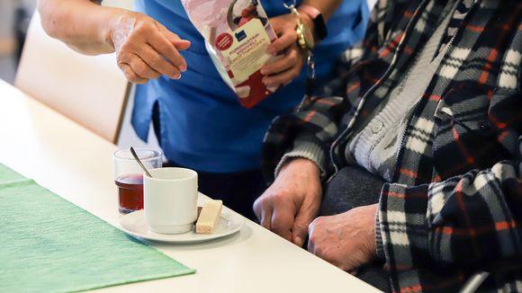 Hoitaja ja vanhus palvelukeskuksessa.