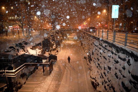 Jalankukija lumipyryssä Helsingin baanalla.