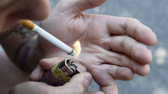 Mies polttaa tupakkaa.