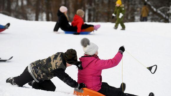 Ihmisiä pulkkamäessä, nauttimassa kauniista talvisunnuntaista Kaivopuistossa Helsingissä.