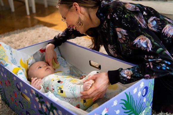 Nainen hymyilee vauvalle, joka makaa äitiyspakkauslaatikossa.