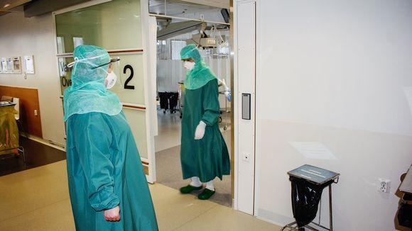 Hoitajia kulkee koronapotilaiden luo ovesta Tyksin teho-osastolla.