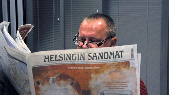 Mies lukee sanomalehteä.