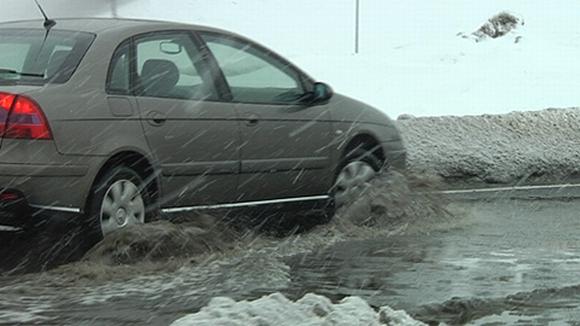 Vettä ja loskaa tiellä. Vesi roiskuu auton ajaessa.