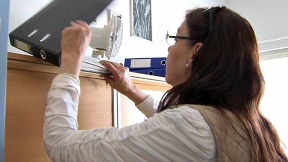 Raija Kuri avaa mapin, joka on sijoitettu toimistokaapin päälle.