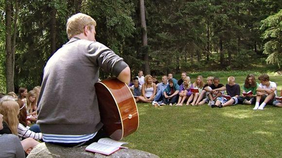 Rippileirillä laulellaan virsiä hieman rennommalla otteella luonnon rauhassa ja kitaran säestyksellä.