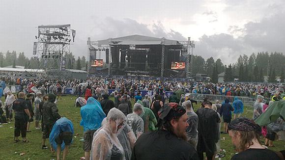 Ihmisiä sadevaatteissa festivaalialueella
