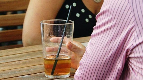 Mies juo olutta pillillä tuopista terassilla.