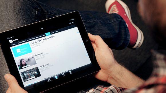 Mies katsoo iPadilla Uutiset-sivustoa Ylen Areenasta.