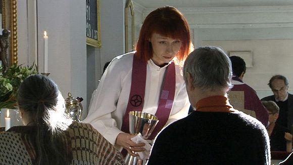 Oulunkylän seurakunnan pastori Marjaana Toiviainen jakaa ehtoollista Helsingin Vanhassa kirkossa.