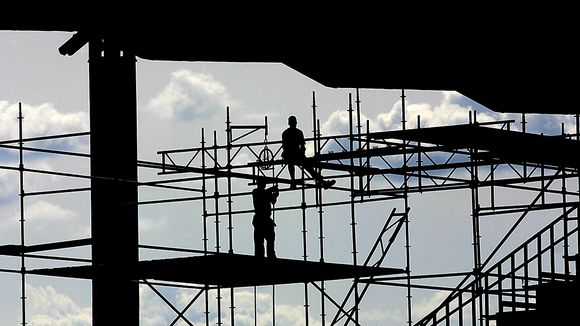 Rakennusmiehiä telineillä siluetissa.