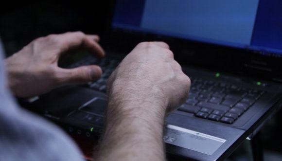 Mies kirjoittaa tietokoneella.