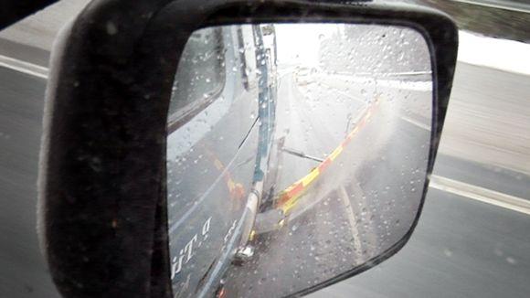 Luminen tie heijastuu aura-auton sivupeilistä.