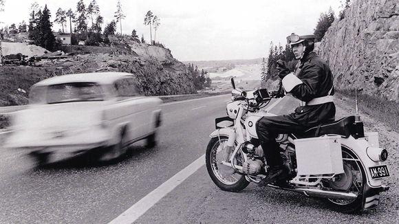 Moottoripyöräpoliisi valvomassa liikennettä maantien varressa.
