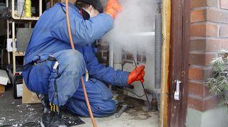 Työmies sulattaa pakkasessa jäätyneitä vesijohtoja.