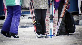Lapset seisoskelevat hiihtovarusteissa.