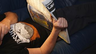 Mies makaa lukee lehteä.