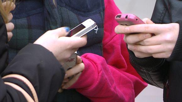 Nuoria käyttämässä kännyköitä.