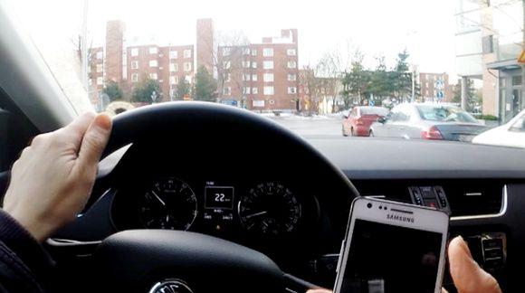 Kuski ajaa autoa puhelin kädessä.
