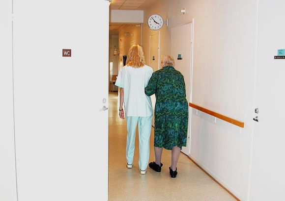 Hoitaja taluttaa vanhusta.
