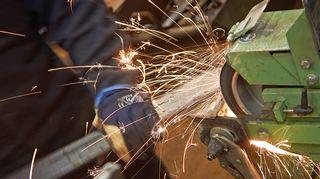Mies työskentelee metallipajalla.