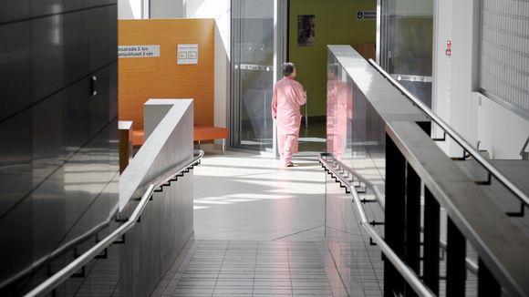 Sairaalan pyjamaan pukeutunut nainen kävelee sairaalan käytävällä.