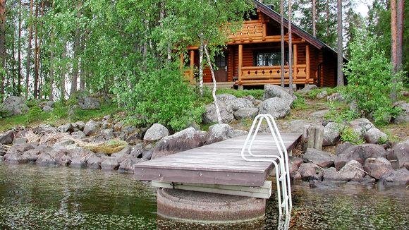 Hirsinen rakennus järven rannalla.