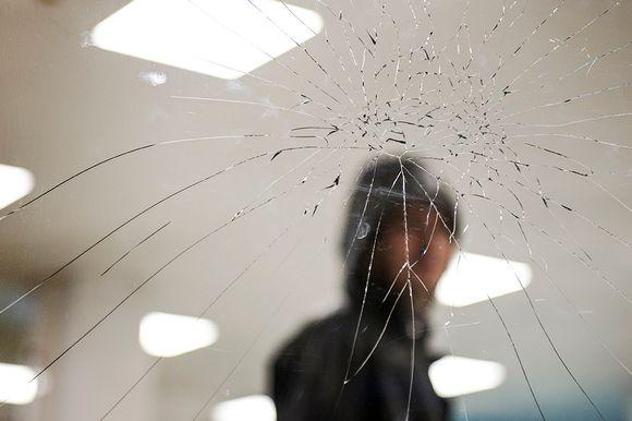 Syrjäytynyt nuori rikkoontuneen lasin takana.